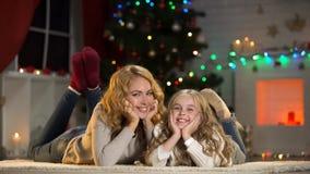 Молодая женщина и девушка лежа под рождественской елкой, усмехаясь к камере, праздники стоковое изображение