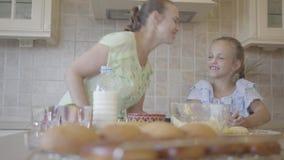 Молодая женщина и ее маленькая дочь варя торты дома в кухне Девушка замешивая тесто, мать видеоматериал