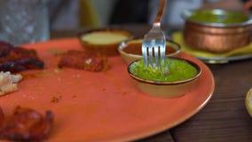 Молодая женщина и ее семья едят индийскую еду в кафе сток-видео