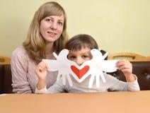 Молодая женщина и жизнерадостная маленькая дочь с добившийся успеха своими силами карточкой дня ` s валентинки карточки подарка Стоковая Фотография