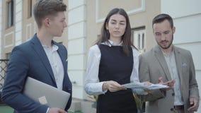 Молодая женщина и 2 люд в официальной носке идя на террасу обсуждая проект Девушка нервная, она бросая вверх бумаги акции видеоматериалы