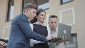 Молодая женщина и 2 люд в официальной носке обсуждая проект на ноутбуке на террасе Отношение дела r видеоматериал