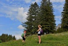 Молодая женщина и мальчик с рюкзаками в горах стоковые изображения rf