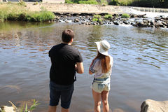 Молодая женщина и человек пока удящ на реке в Баварии Стоковое Фото