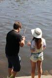 Молодая женщина и человек пока удящ на реке в Баварии Стоковая Фотография RF
