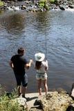 Молодая женщина и человек пока удящ на реке в Баварии Стоковое фото RF