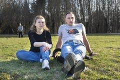 Молодая женщина и человек сидя на лужайке в парке на траве Стоковое фото RF