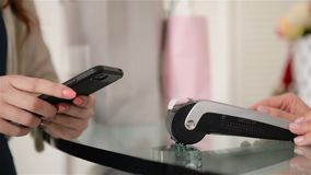 Молодая женщина как клиент оплачивает cashless с приложением смартфона на терминале карты сток-видео