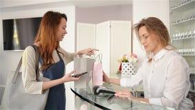 Молодая женщина как клиент оплачивает cashless с приложением смартфона на терминале карты акции видеоматериалы