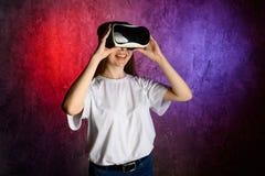 Молодая женщина касаясь воздуху во время опыта VR Голубая и красная предпосылка стоковые изображения