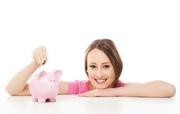 Молодая женщина кладя деньги в piggy банк стоковая фотография