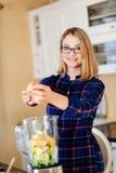 Молодая женщина кладя фрукты и овощи в eletrical blender стоковое изображение rf