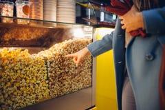 Молодая женщина комплектует попкорн на кино еда и закуски стоковые изображения rf