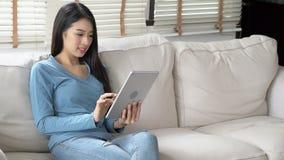 Молодая женщина красивого портрета азиатская используя планшет с улыбкой и счастливым усаживанием на кресле на живя комнате, деву