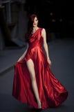 Молодая женщина красотки в порхая красном платье стоковые изображения rf