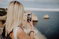 Молодая женщина красоты принимает фото по телефону красивого ландшафта океана с водой и скалой в Португалии перемещение карты dub стоковая фотография rf