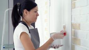Молодая женщина крася краску стены в квартире или доме акции видеоматериалы