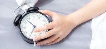 Молодая женщина крупного плана вебсайта знамени азиатская поворачивает будильник внутри стоковые фото