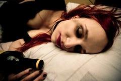 Молодая женщина лежа в кровати с бутылкой вина Стоковая Фотография RF