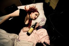 Молодая женщина лежа в кровати с бутылкой вина Стоковые Фото