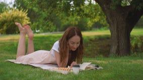 Молодая женщина лежа и читая книгу в парке акции видеоматериалы