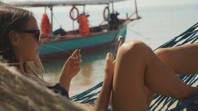 Молодая женщина лежа на гамаке с умной карточкой телефона и банка на песчаном пляже видеоматериал