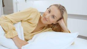 Молодая женщина лежа на ее кровати в утре акции видеоматериалы