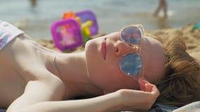 Молодая женщина лежа на пляже сток-видео