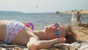 Молодая женщина лежа на пляже видеоматериал