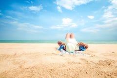 Молодая женщина лежа на тропическом пляже, ослабляет с шляпой Стоковые Изображения RF