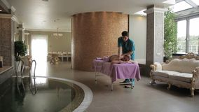 Молодая женщина лежит на встрече массажа на салоне курорта сток-видео