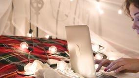 Молодая женщина лежит на кровати с компьтер-книжкой на предпосылке гирлянды, видео- болтовне, делает онлайн приобретение видеоматериал