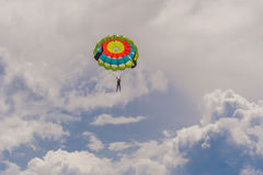 Молодая женщина летает на парашют среди облаков стоковая фотография rf