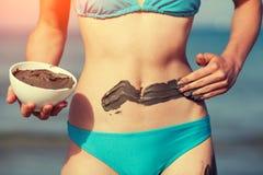 Молодая женщина мажа маску грязи на теле стоковое изображение