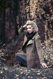 Молодая женщина моды в классическом бежевом пальто идя в лес осени Стоковое Изображение RF