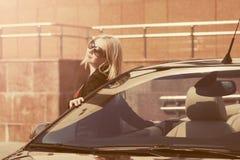 Молодая женщина моды в солнечных очках полагаясь на ее обратимом автомобиле стоковое изображение