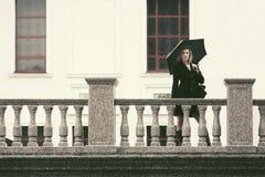 Молодая женщина моды в черном пальто с зонтиком идя в улицу города стоковая фотография rf