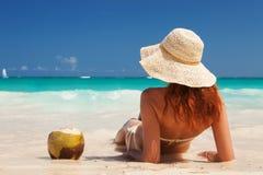Молодая женщина моды ослабить на пляже Счастливый образ жизни острова Белый песок, голубое облачное небо и кристаллическое море т стоковое изображение