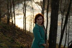 Молодая женщина моды ослабляя и наслаждаясь заход солнца около реки в  стоковое фото rf
