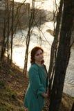 Молодая женщина моды ослабляя и наслаждаясь заход солнца около реки в  стоковое изображение rf