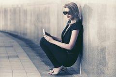 Молодая женщина моды при цифровой планшет сидя на стене Стоковая Фотография