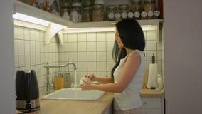 Молодая женщина моя пакостные блюда с мылом и говоря к кто-то в домашней кухне стоковое фото rf