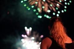 Молодая женщина наблюдает фейерверки стоковое изображение rf
