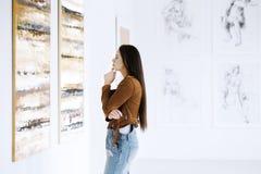 Молодая женщина наблюдающ картиной стоковые фото
