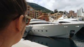 Молодая женщина наблюдающ яхтами в порте, туристский ослаблять на взморье, крупном плане акции видеоматериалы