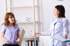 Молодая женщина навещая женский физиотерапевт доктора стоковые изображения