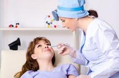 Молодая женщина навещая женский otolaryngologist доктора стоковая фотография rf