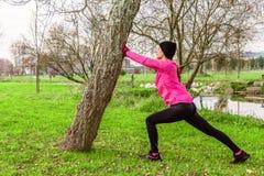 Молодая женщина нагревая и протягивая ноги перед бежать на холодной зиме, осень дня падения в городском парке стоковое фото rf