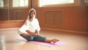 Молодая женщина нагревая сидеть на циновке йоги и делать тренировки ноги - студию танца акции видеоматериалы