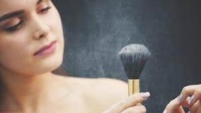 Молодая женщина нажимает щетку с его рукой Кожа летает над черной предпосылкой t Применение макияжа внутри сток-видео